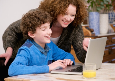 mother on a laptop at home with her child